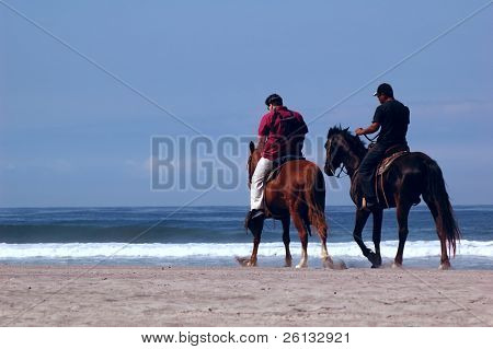 A tourist and a cowboy ride horses down an ocean beach