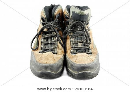 Pair of old dirty hiking boots isolated on a white background