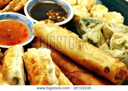 Plate of dim sum, egg rolls, shumai, and pot stickers with dipping sauce