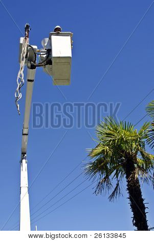 A utility company electrician stands in a bucket boosted by a boom crane as it maneuvers towards power lines during installation of a new power pole