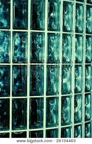Closeup of a greenish blue glass brick wall inside a building