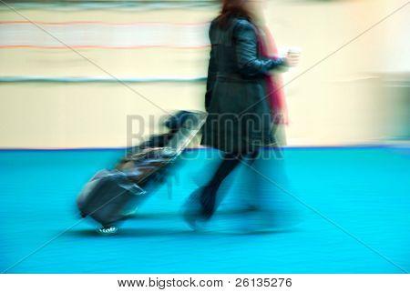 Female traveler rushing through an airport terminal
