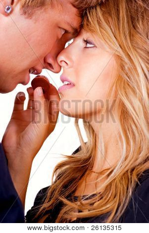 Young woman feeds a chocolate candy to her boyfriend