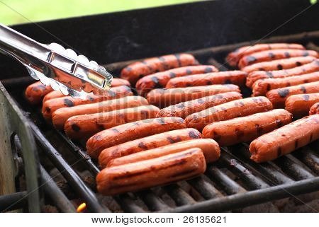 Rows of hot dogs on barbeque grill at park