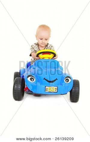 toddler boy driving a toy car over white