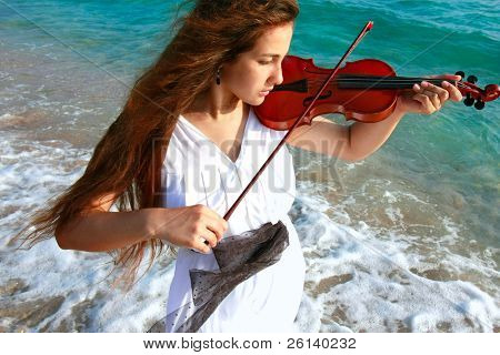 young attractive woman playing violin on sea background