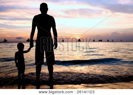 father and son on sunset sea background