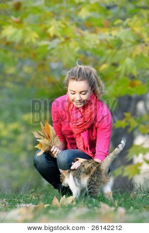 attractive young girl and cat on natural background