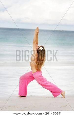 young attractive woman doing yoga on beach