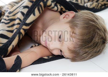 young cute boy in counterpane