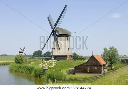 The archetypal image of the Netherlands; a quaint scene, with a barn, two windmills, and a lush, reed covered canal, meandering through the rural landscape