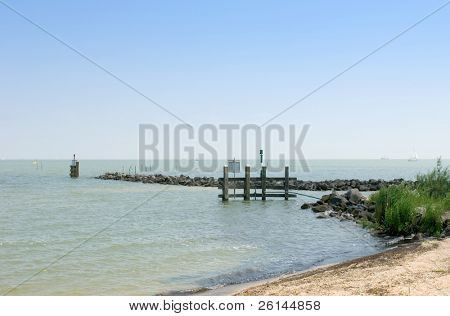 A tranquil summer day at the IJsselmeer, the Netherlands, with gently rippling water, a storm breaker with the various navigational elements, (beacons, navigational lights and such