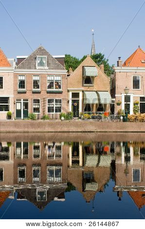 The quaint village of Spaarndam, the Netherlands, with it's old, picturesque houses reflected in the water on a warm summer morning, basking in the light