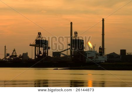 Two cranes used in a steel plant to unload the raw materials, such as iron ore and coal just after sunset.