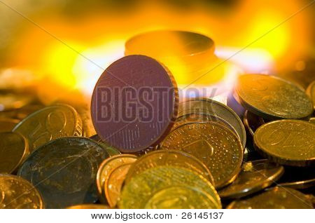 A glowing red hot coin in front of the blue flames of burning natural gas, a metaphor of wasting energy, not only bad for the environment, but also a waste of money