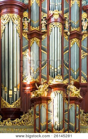 A close up of a church organ with pipes in various sizes, lit by the bright light coming through the church windows.
