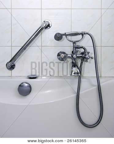 Details of a vintage bathroom, with a tap, a hand-held shower, and a handrail, all chromed metal elements.