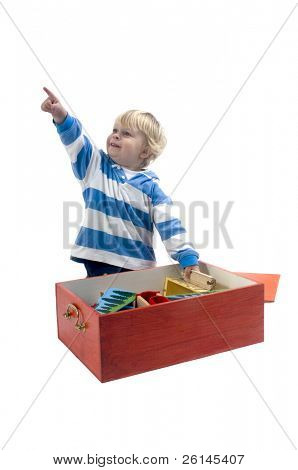 A 3 year old boy playing with a wooden train, and pointing