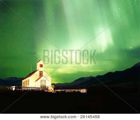 Uma igreja iluminada com a magnífica Aurora Borealis, ou norte da luz iluminando o céu em