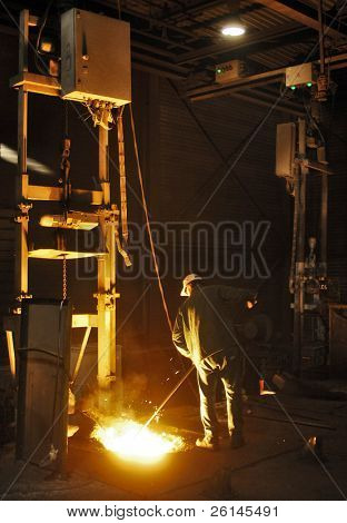 A man working in a cast iron factory close to the melting pit of the foundry