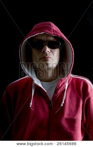 A grim looking Hoodlum wearing sunglasses, and looking mean