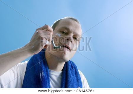 a middle aged man dressed in a white t-shirt, shaving himself