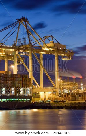 The unloaing of a cargo vessel using huge overhead cranes and carts, transporting the containers to and from the ship. Some smoke stacks in the distance