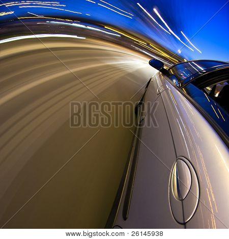 Un coche conduciendo a alta velocidad a través de un tramo curvo de la autopista