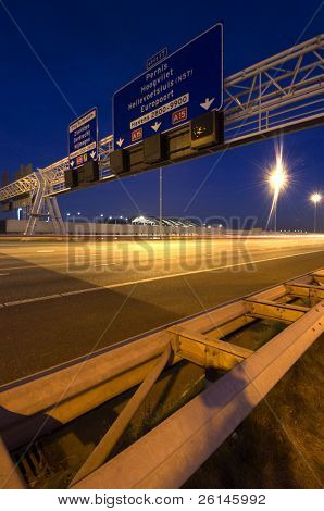 Steel structures, supporting traffic signs and direction information systems above a motorway at night