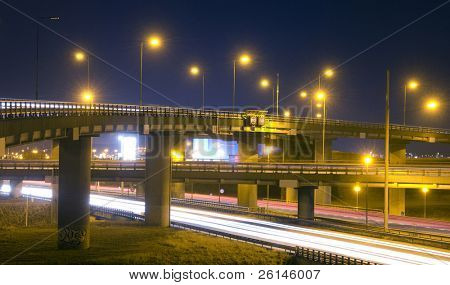 A motorway junction at night, with various fly-overs, crossing each other