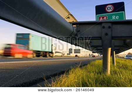 A motorway safety rail with route information sign and motion blurred passing cars