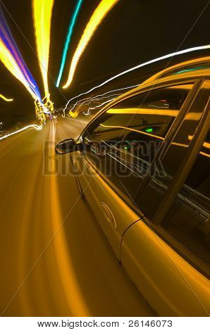 A car speeding towards the horizon on an uneven road, surrounded by colorful lights overhead.
