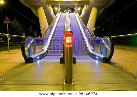Two escalators, one moving, the other standing still, leading up towards the entrance of the platform of an elevated tram line