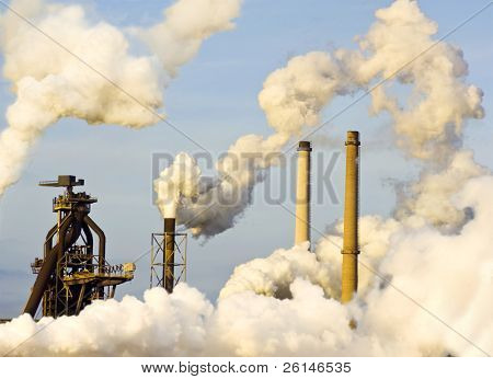 The top of a blast furnace and several smoke stacks, emitting steam, lit by the warm light of the evening sun