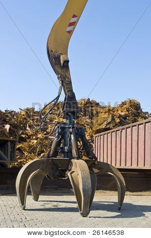 A claw, attached to a huge crane in front of a scrap heap