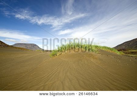 A volcanic sand dune with two table mountains in the background arond the Hiodufell volcano volcano in the katla volcanic system in Iceland.