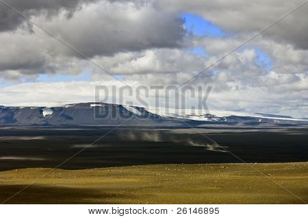 The trail of dust is the tell tale of an approaching car in the barren, empty Sprengisandur Highlands of Iceland, with the dominating Vatnajokull glacier and volcano in the background