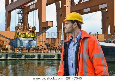 Un ingeniero, viendo de cerca la descarga de un barco de contenedores en un entorno de Puerto