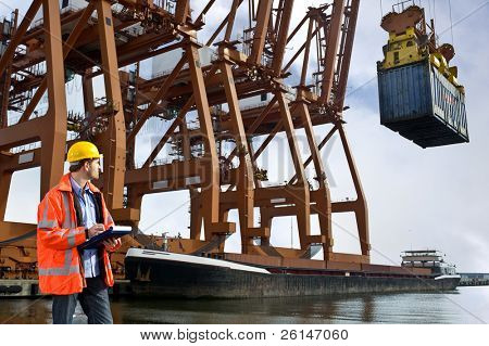 A customs officer checking containers being unloaded at a commercial harbor