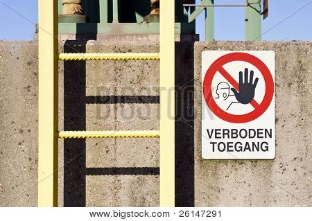 A ladder and no access warning sign on a concrete pillar at an industrial plant