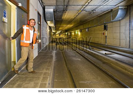 A sturdy looking engineer, closing a door to a maintenance room behind him inside a public transportation tunnel, looking relaxed and with a flashlight in his hand