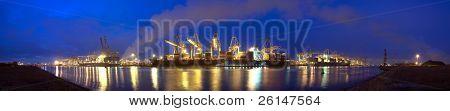 Una imagen panorámica de tres buques portacontenedores descargado por la noche en un puerto comercial ocupado, ingenio