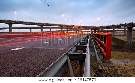 A highway overpass with busy traffic at night. Various roads intertwining with each other