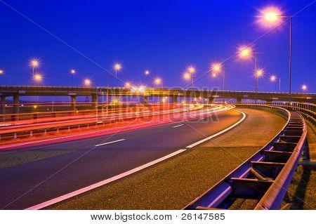 Autos, die auf eine Überführung einer Autobahn Nachts brechen
