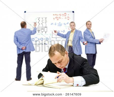 A manager, trying to understand some very complex theories, oblivious of the people in the background trying to explain it to him