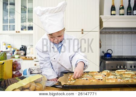 A small boy, dressed up as a chef, garnishing the sweet bread he baked in a cluttered kitchen