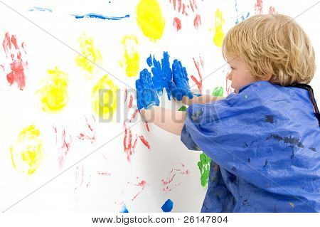 A young boy pressing his hands, covered with blue paint, against a wall, making prints with finger paint