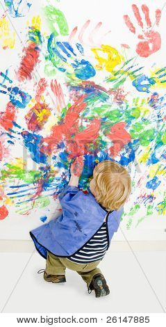 Young boy busy finger painting, kneeling down, to finish hsi work