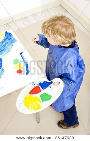 A young boy, standing next to a table with a big sheet of paper on a cardboard surface with a palette with poster paint in his hands, painting a traffic light