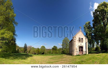 An old, small, chapel on a knoll surrounded by huge trees on a lush spring afternoon